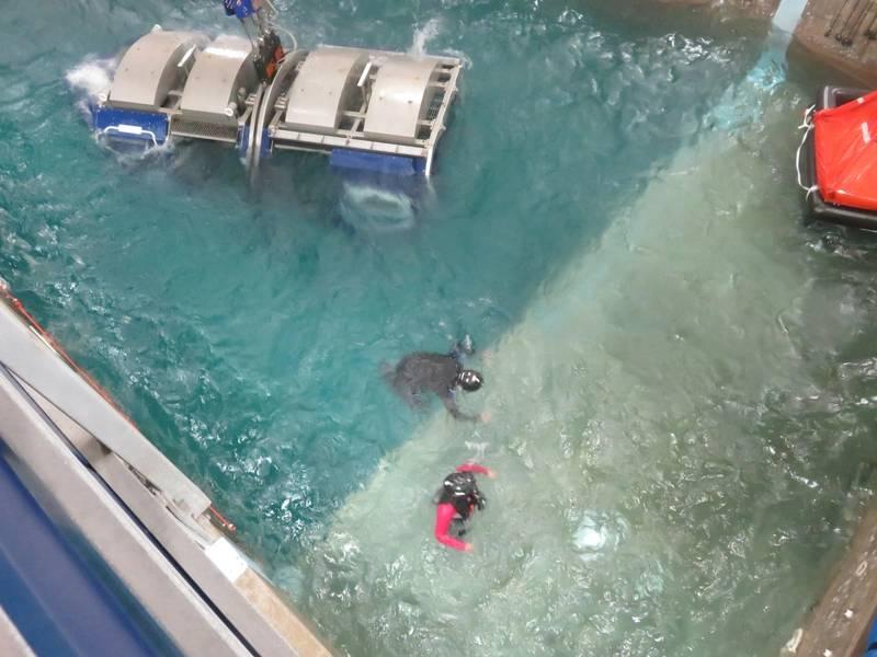 गोताखोर (काले रंग में) ऑफशोर वर्कर (लाल रंग में) को तस्वीर के दाईं ओर जीवन की सुरक्षा तक पहुँचने में सहायता करता है। (फोटो: टॉम मुलिगन)