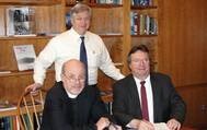 Eric Larsson (standing), Director of Maritime Education, and SCI's President & Executive Director, the Rev. David M. Rider (L), sign the contract for the first phase of SCI's Houston simulator upgrades with Kongsberg Maritime, represented by Area Sales Manager Henry Tremblay (R).