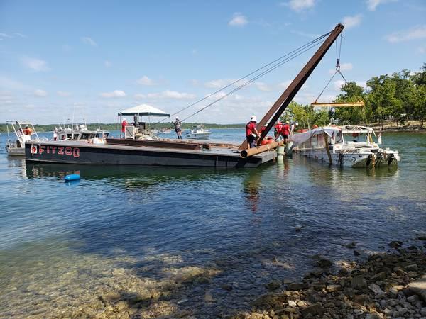 米国沿岸警備隊は、2018年7月23日、ミズーリ州ブランソンのテーブルロック湖からStretch Duck 7を撤去することを監督しています。ミズーリ州高速道路のパトロール・ダイバーが船舶を艤装した後、海岸に曳航する前にバージ・クレーンを持ち上げ安全な施設に輸送するためのフラットベッドトレーラーに積み込まれています。 (Lora RatliffによるUS Coast Guardの写真)
