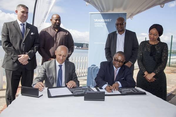 Frente: Gianluca Suprani (izquierda, de la Terminal de cruceros KwaZulu) y Siyabonga Gama (derecha, consejero delegado del grupo Transnet) sellan el acuerdo del operador terminal para la nueva terminal de cruceros de Durban, flanqueada por (espalda, izquierda a derecha) Ross Volk, Nkululeko Mchunu, Moshe Motlohi (COO interino de Transnet National Ports Authority) y Shulami Qalinge (Directora ejecutiva de Transnet National Ports Authority).