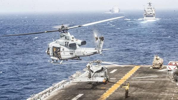 Um helicóptero Venom UH-1Y designado para o Esquadrão Tiltrotor Médio Marinho (VMM) 163 (Reinforced), 11ª Unidade Expedicionária dos Fuzileiros Navais (MEU), decola do convés de vôo do navio anfíbio USS Boxer (LHD 4) durante um trânsito estreito. O Grupo Anfíbio Pronto Boxer e o 11º MEU estão implantados na área de operações da 5ª Frota dos EUA em apoio às operações navais para garantir a estabilidade e a segurança marítima na Região Central, conectando o Mediterrâneo e o Pacífico através do oeste.