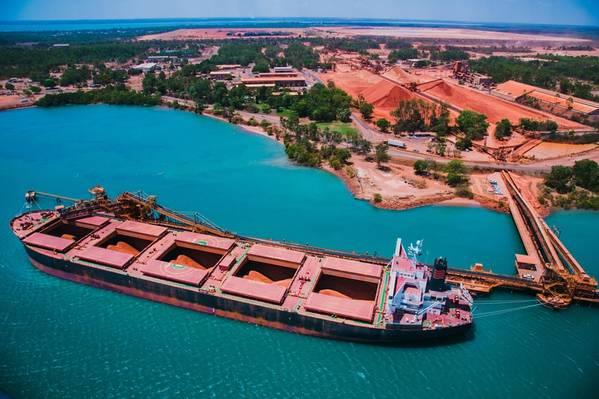 在Rio Tinto Weipa运输的船在背景中用铝土矿库存装载。版权所有©2018力拓。