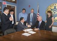 The fifth largest steel producer in the world, South Korea's POSCO, announced it will build a wire rod processing center at the Port of Indiana-Jeffersonville. Left to right Woon Hyun Yeo, Sales Director, POSCO; Kyu Tae Kim, Finance Director, POSCO; Kenny Hwang (sitting), President, POSCO-AAPC; Rob Waiz, Economic and Re-development Director, City of Jeffersonville; Mike Moore, Mayor, City of Jeffersonville; Scott Stewart, Port Director, Port of Indiana-Jeffersonville; Wendy Dant Chesser, CEO, On