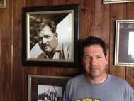 ohn Hemingway poses next to photo of grandfather Ernest Hemingway at the Bimini Big Game Club Resort.