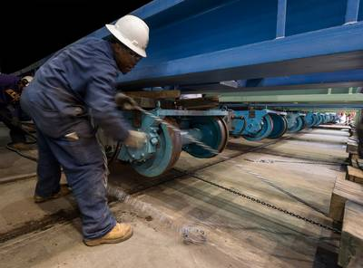 Alexander Manning pulls a piece of track into position at Newport News Shipbuilding under a transfer car for the submarine John Marner (SSN 785). Photo by Chris Oxley