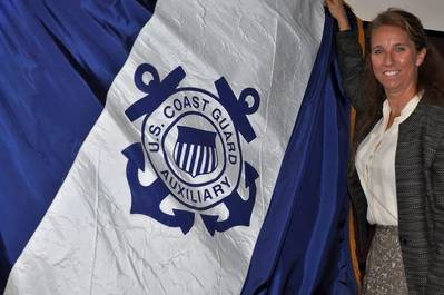 Michelle Thornton holds up the Coast Guard Auxiliary flag at Atlantic Area Command in Portsmouth, Va., July 6, 2015. Thornton, who works as a civilian employee for the Coast Guard, volunteers more than 20 hours every week to the Coast Guard Auxiliary where she serves as the district captain for Hampton Roads. (USCG photo by Melissa Leake)