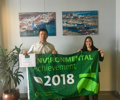 Photo caption: Henry Pak,  General Manager of Terminal Management, USA, at SM Line Corp., was recently presented with a Green Flag by Wendy Fung, Business Development Manager, Exports, at the Port of Long Beach. SM Line was recognized for voluntarily slowing its vessels to 12 knots or less within 40 miles of the Port.(Photo: Port of Long Beach)