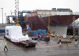 The Rolls-Royce MT30 gas turbine enclosure, shrink wrapped for protection, arrives alongside HMS Queen Elizabeth, prior to installation at Babcock's Rosyth yard in Scotland.