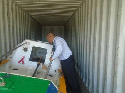 Victor Mooney of Queens, New York looks at the Spirit of Malabo inside a shipping container at the Haitian Coast Guard base in Cap Haitian today.