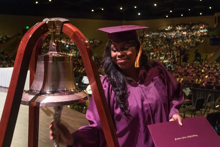 Apprentice School graduate Tiffani Brown Powell, coatings specialist, rang the Apprentice School bell, a tradition during the commencement exercises. Photo by Matt Hildreth.
