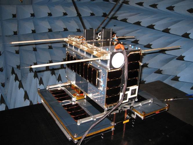NORsat-1 in EMC test at SFL. Two AIS antennas may be seen at the top, and four Langmuir probes off to the sides. The solar wings of the satellite are at the bottom. (Photo: Space Flight Laboratory)