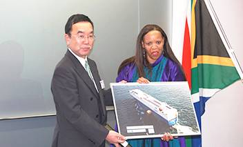 "A Panel of MOL's cutting-edge hybrid car carrier ""Emerald Ace"" ,which carried eight mobile library vehicles last year, was presented to South African Ambassador in Japan Her Excellency Mohau Pheko by MOL Senior Managing Executive Officer Takashi Kurauchi."