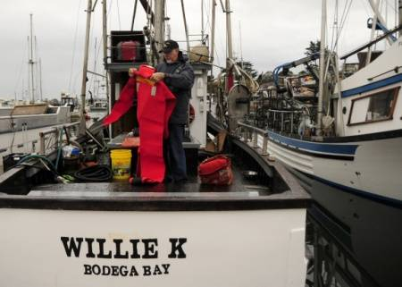 Ronald Kram, a Coast Guard Auxiliarist, inspects an immersion suit aboard the Willie K, a crab vessel moored in Spud Point Marina in Bodega Bay, November 8, 2012. (U.S. Coast Guard photo by Pamela J. Boehland)